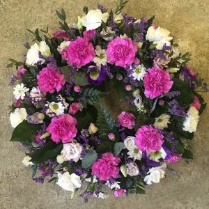 a funeral wreath by Flowers for You, Dalbeatte in purple and white