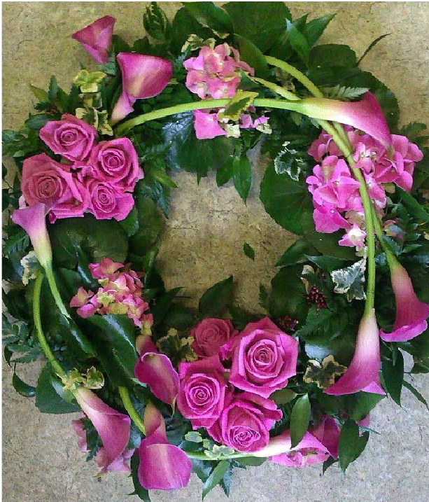 A funeral wreath from Flowers for You, Dalbeattie, using deep pink roses and pink calla lilies