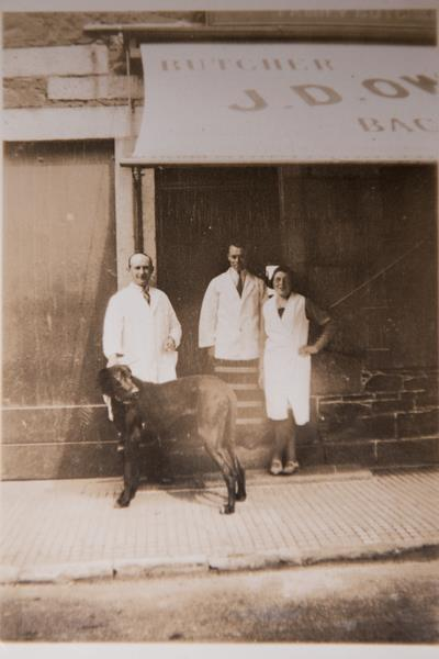 The Owen family in years gone by, standing in front of the Newton Stewart shop with their Great Dane