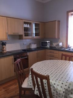 The large modern kitchen with dining table, fitted appliances and all mod cons