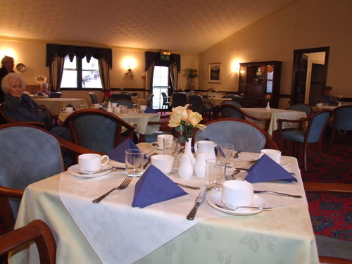 The dining room with tables for 4, freshly laundered tablecloths and comfy seating