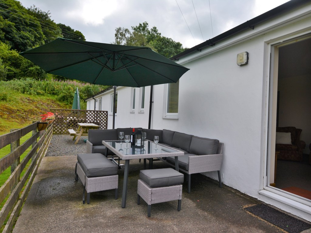 The lovely patio furniture on the terrace includes an umbrella to shade visitors from the sun