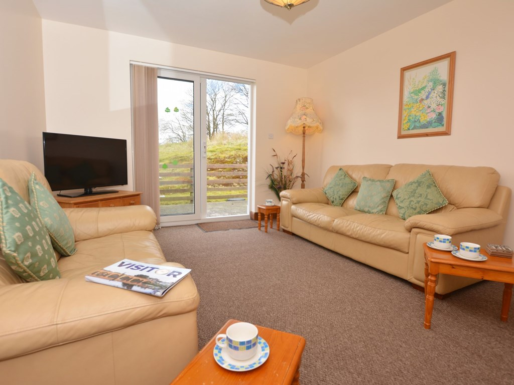 The bright spacious lounge of Creeview Holiday Cottage with its French window and leather settees