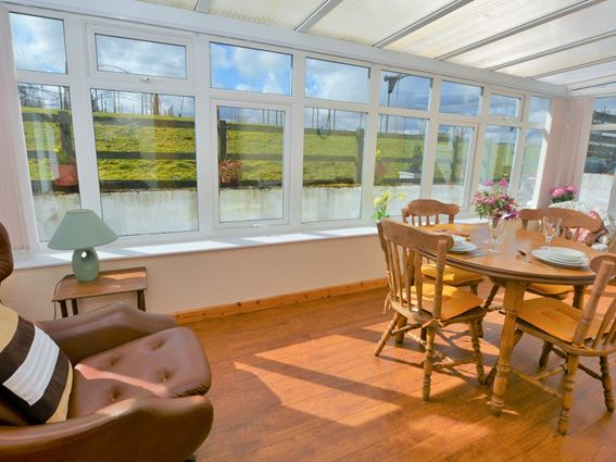 The sun bathed conservatory dining room of Carty Holiday Cottage, Barrhill Farm, Newton Stewart