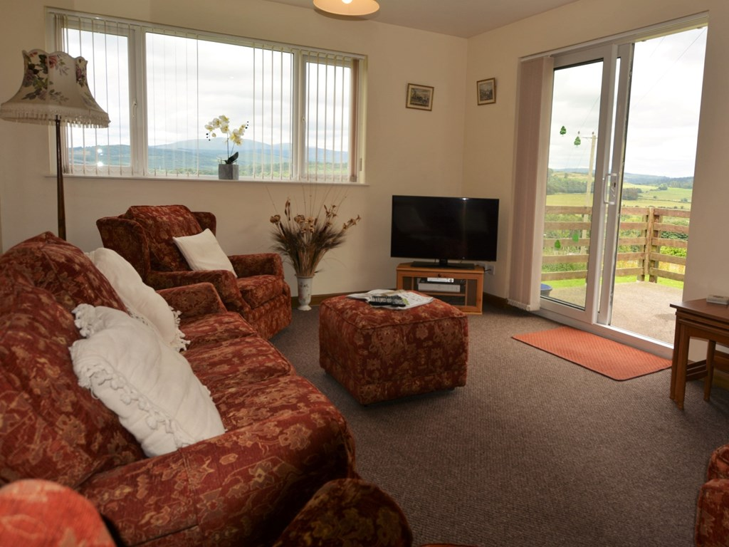 The lounge at Cairnsmore holiday accommodation has patio doors looking out over the countryside