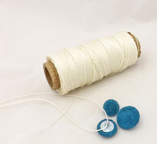 Reel of button twine with three velvet buttons
