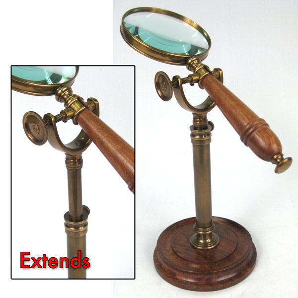 Wooden handled magnifying glass on an antique brass and rosewood stand
