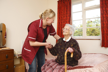 A member of staff helping a resident out of bed