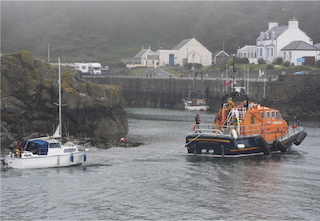 The Porpatrick RNLI lifeboat tows a small vessel into Portpatrick Harbour