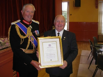 Tommy Henderson, Chairman is pictured receiving the certificate and Crystal Ware from Lt. Col. Sir Malcolm Ross in 2009.