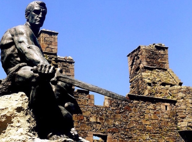 Statue of a seated man with a sword in front of MacLellan's Castle in Kirkcudbright
