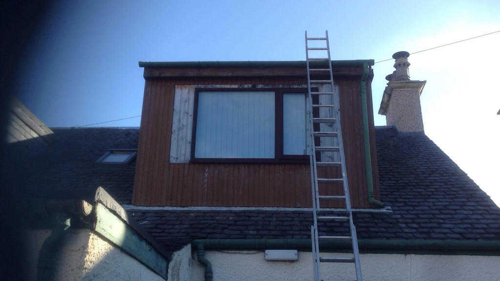 Ladder up against a dormer window prior to treatment