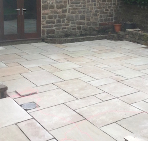 A completed sandstone block pave patio with drainage