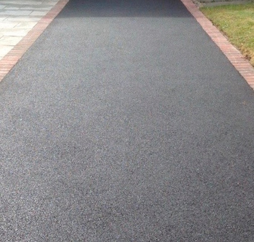 Long tarmac drive with red brick edging in Northants