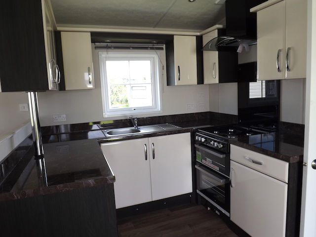 An example of a fitted kitchen in a static caravan with stylish units, cooker, hood and plenty storage space