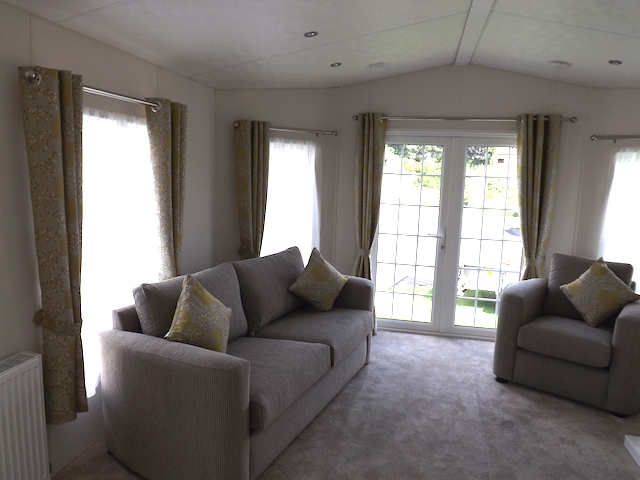 An example of a lounge in a static caravan at Penpont Holiday Park with double French doors leading outside
